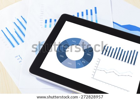 digital tablet, graph,chart on work table.  - stock photo