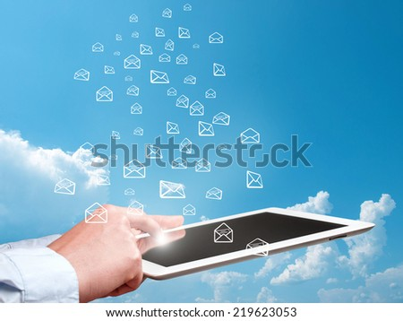 digital tablet in hand and sending e-mails - stock photo