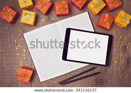 Digital tablet mock up template with gift boxes and notebook on wooden desk. View from above - stock photo