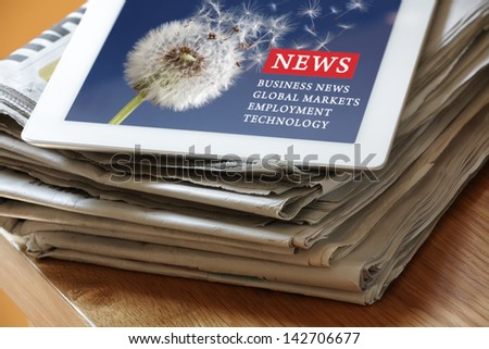 Digital tablet on newspaper concept for internet and electronic news - stock photo
