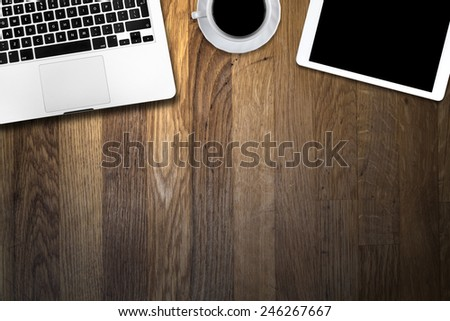 digital tablet pc, computer and cup of coffee on wooden table - stock photo