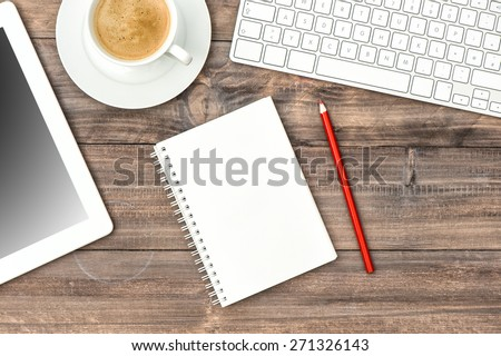 Digital tablet pc, keyboard and cup of black coffee on wooden table. Home office workplace - stock photo