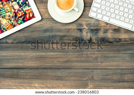 digital tablet pc, keyboard and cup of coffee on wooden table. workplace with christmas picture on display. winter holidays concept. retro style toned picture - stock photo