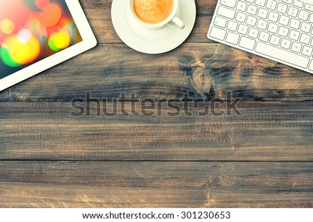 Digital tablet pc, keyboard and red cup of coffee on wooden table. Vintage style toned picture with light leaks - stock photo