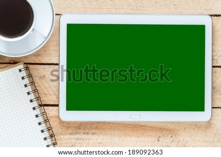 Digital tablet pc on business desk with blank green screen - stock photo