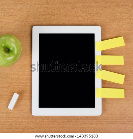 Digital tablet with a black empty display with post-it notes stuck on the side over a school desk next to an eraser and a green apple - stock photo