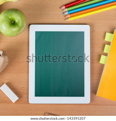 Digital tablet with blank screen over a school desk between a paper notebook, pencils, an eraser, and an apple - stock photo