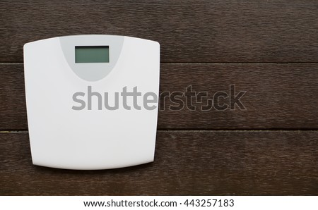 Digital weight scale on wooden background.bathroom digital scale  - stock photo