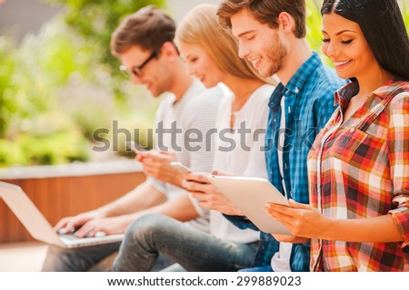 Digital world. Group of happy young people holding different digital devices and smiling while sitting in a row outdoors - stock photo