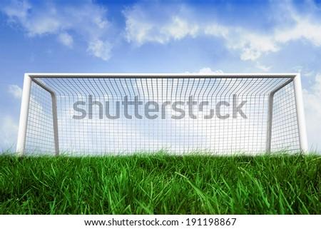 Digitally generated goalpost on grass under blue sky - stock photo
