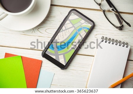 Digitally generated image of map against overhead view of an desk - stock photo