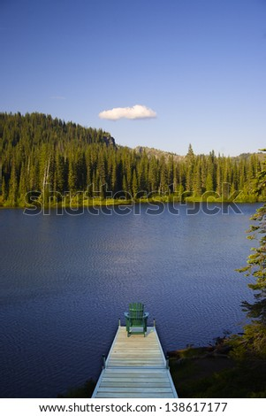 Digitally manipulated image of an adirondack chair sitting on a dock with a lake in the background. - stock photo