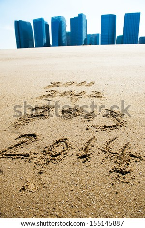 digits 2013 and 2014 on the sand seashore  - stock photo