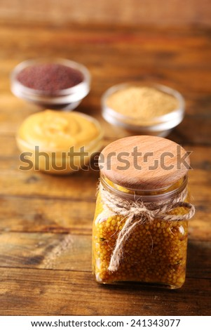 Dijon Mustard in glass jar  and mustard seeds and sauce in bowls on wooden background - stock photo