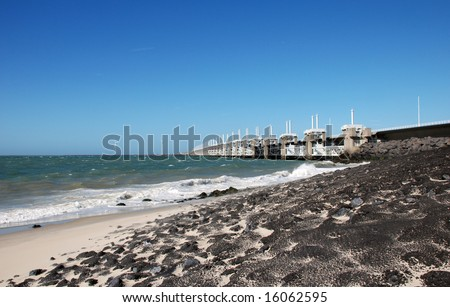 Dike beach and oosterschelde flood barrier - stock photo