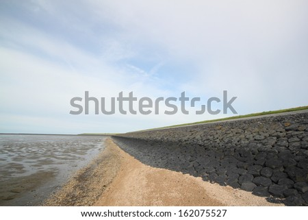 dike, mudflat on the left, near bensersiel, germany - stock photo