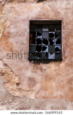 Dilapidated industrial building, chipped and cracked wall, and broken window - stock photo