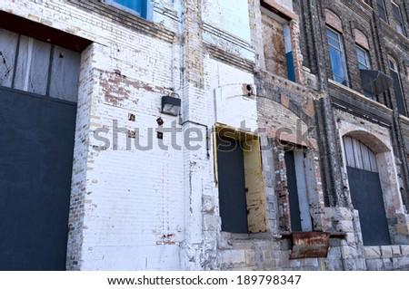 Dilapidated warehouse building exterior and crumbling dock bays - stock photo