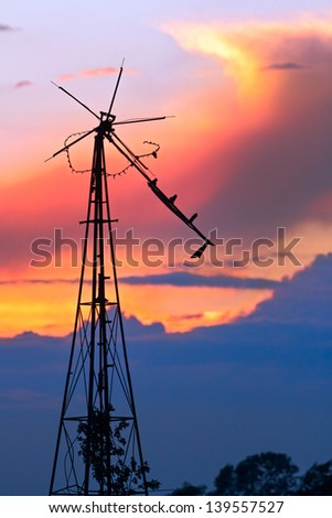 Dilapidated windmill at Sunset has seen better days. Photographed in Central Indiana near Monrovia. - stock photo