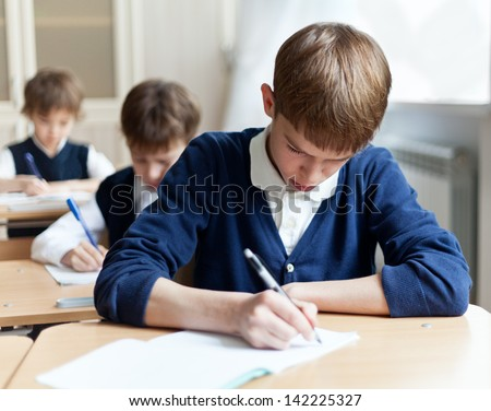 Diligent preschool sitting at desk, classroom - stock photo