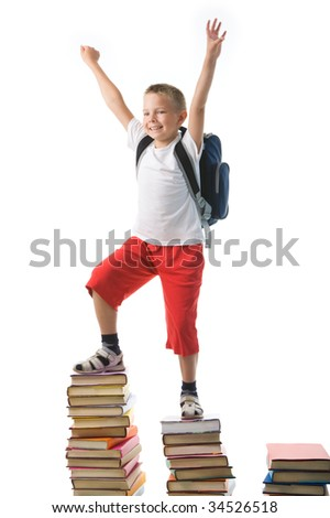 Diligent preschooler standing on the top of book stairs with his arms raised - stock photo