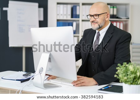 Diligent senior businessman working at his desk in the office on a desktop computer, reading information on the monitor - stock photo