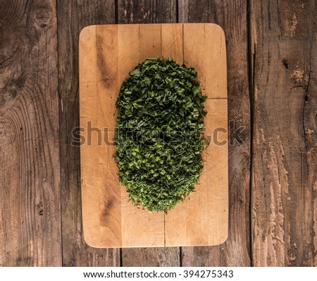 dill and parsley on wooden chopping board  - stock photo
