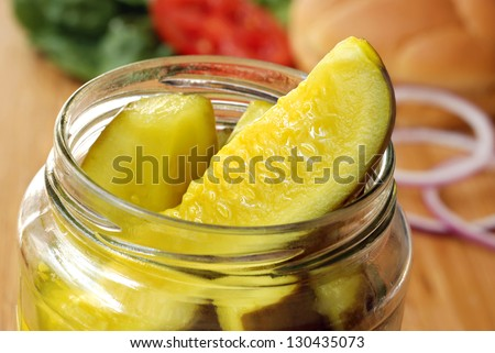 Dill pickle spears in open jar with sandwich ingredients in soft focus in background.  Macro with shallow dof. - stock photo