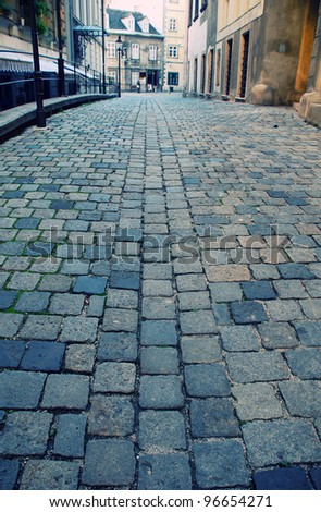 Diminishing view of old european street with cobblestone close-up(Vienna,Austria). Selective focus - stock photo