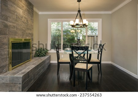 Dining area in upscale home with magnificent fire place. - stock photo