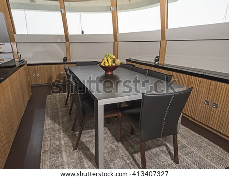 Dining area with table and chairs on large luxury motor yacht - stock photo