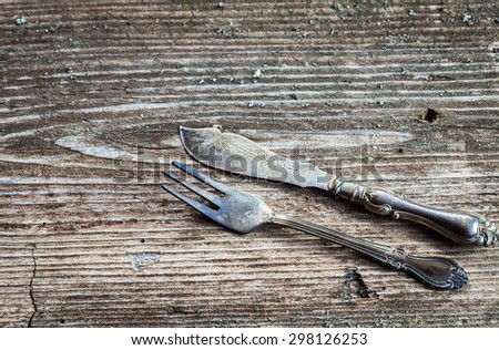 Dining fork and knife on rustic background, copy space, top view - stock photo