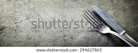 Dining fork and knife on rustic vintage background with copyspace - stock photo