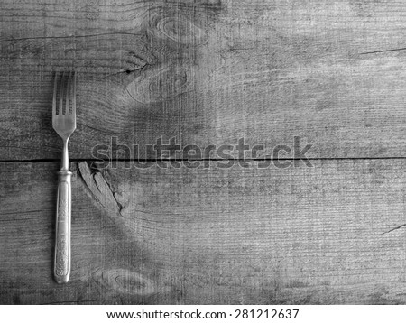 Dining fork on cotton napkin on raw wooden background. Grunge style. - stock photo