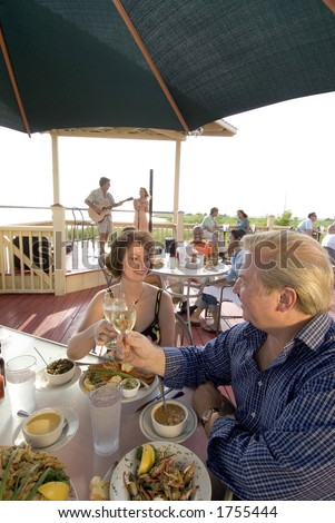 dining outside on the deck of a bayside restaurant - stock photo