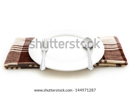 Dining place setting. A white plate with silver fork and spoon isolated on white background - stock photo