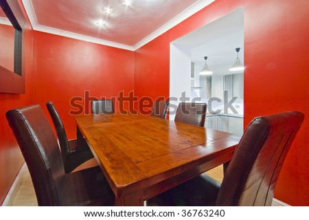 dining room in red with massive wooden table and leather seats - stock photo