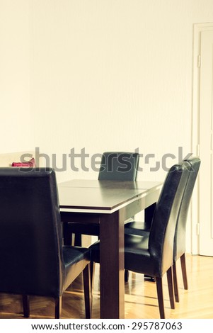 Dining room interior with table and four black chairs near kitchen. Breakfast Area spot. Space for work and business meetings with clients and people. Indoor photo - stock photo