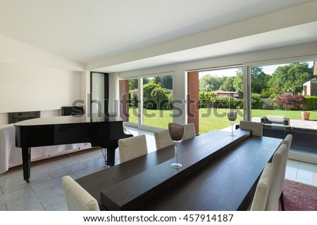 Dining room with piano of a modern house, interior - stock photo