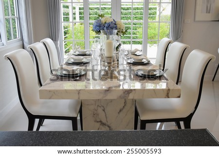 dining table and comfortable chairs in vintage style with elegant table setting - stock photo