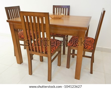 Dining table and four chairs in an apartment against white wall - stock photo