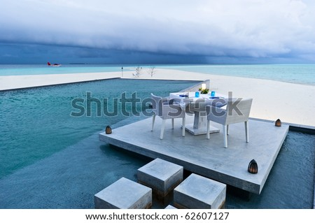 dining table on the deck of outdoor swimming pool in beach resort - stock photo