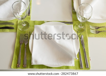 Dining table set for a wedding or corporate event. Lunch table set up. Plate with napkin, silverware and wineglass. Close up. - stock photo