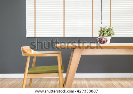 Dining table set with chair in the cozy dining room. wood table, wood chair, dining room, minimalist, empty table, white blinds, laminate floor, close up, furniture, plant pot and dark grey wall - stock photo