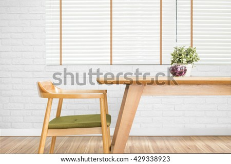 Dining table set with chair in the cozy dining room. wood table, wood chair, dining room, minimalist, empty table, white blinds, laminate floor, close up, furniture, plant pot and brick wall - stock photo