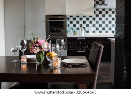 Dining table set with flowers, candles and glasses in the interior of modern kitchen - stock photo