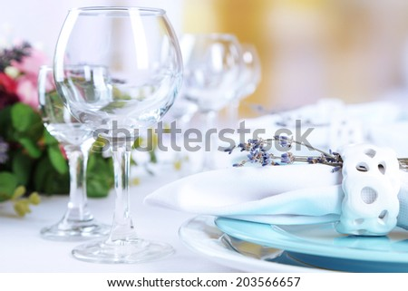 Dining table setting with lavender flowers on table, on bright background. Lavender wedding concept - stock photo