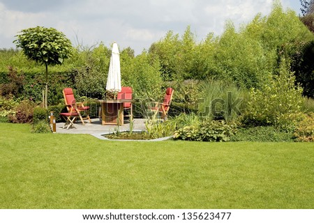 dining table with chairs and parasol in a lush garden - stock photo