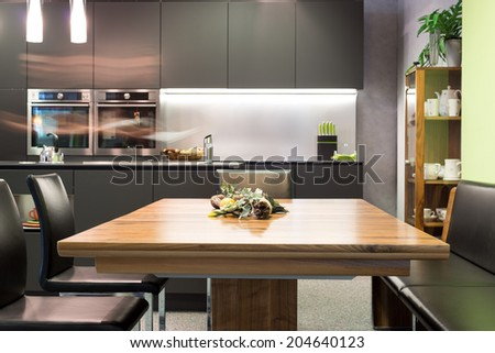 dining table with leather chairs and dark grey modern kitchen - stock photo