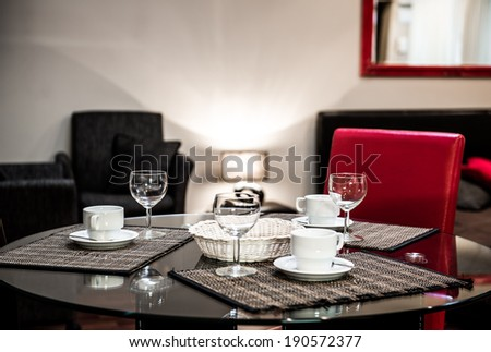 Dining table with the empty coffee cups and glasses - stock photo